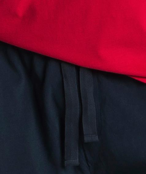 Piżama męska składa się z dwóch części: krótkich spodenek (szortów) w kolorze granatowym oraz gładkiej koszulki w kolorze czerwonym z napisem ATLANTIC #2