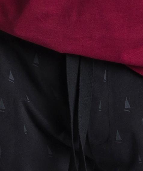 Męska piżama składa się z dwóch części: długich spodni w kolorze ciemno grafitowym, ozdobionych niewielkich rozmiarów szarymi wzorami w żaglówki oraz ciemno czerwonej bluzy z długimi rękawami i widocznym logo marki po lewej stronie #2