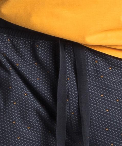 W skład męskiej piżamy wchodzą dwie części: długie spodnie w kolorze granatowym, które ozdobione są niewielkich rozmiarów graficznymi wzorkami oraz gładka koszulka z krótkimi rękawami, w intensywnie żółtym kolorze #2